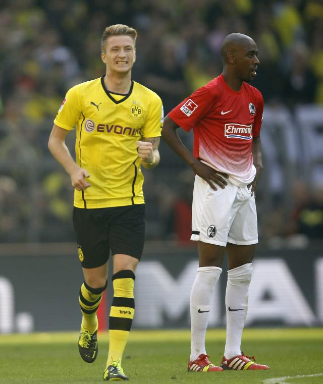 Borussia Dortmund's Marco Reus (L) celebrates a goal against Freiburg during the German first division Bundesliga soccer match in Dortmund September 28, 2013. REUTERS/Ina Fassbender (GERMANY - Tags: SPORT SOCCER) DFL RULES TO LIMIT THE ONLINE USAGE DURING MATCH TIME TO 15 PICTURES PER GAME. IMAGE SEQUENCES TO SIMULATE VIDEO IS NOT ALLOWED AT ANY TIME. FOR FURTHER QUERIES PLEASE CONTACT DFL DIRECTLY AT + 49 69 650050