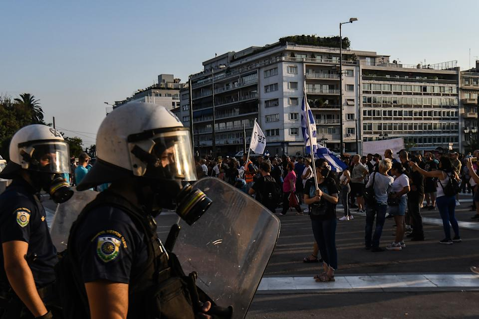 ATHENS, GREECE - JULY 24: Anti-vaccine protesters hold a banners and wave flags as they march to the parliament, in Athens, on Saturday, July 24, 2021. Thousands of people protested against Greek government's measures to curb rising COVID-19 infections. (Photo by Dimitris Lampropoulos/Anadolu Agency via Getty Images)