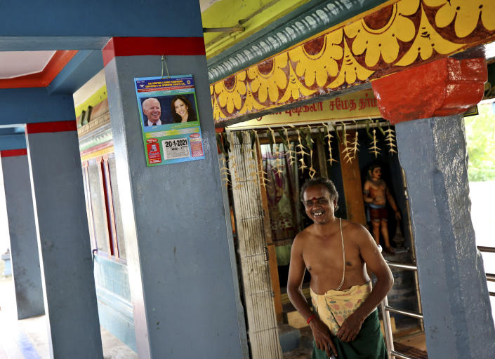 A Hindu priest stands next to a calendar featuring photographs of U.S. President-elect Joe Biden and Vice President-elect Kamala Harris on a wall of the temple where special prayers were held for Harris ahead of her inauguration, in Thulasendrapuram, the hometown of Harris' maternal grandfather, south of Chennai, Tamil Nadu state, India, Wednesday, Jan. 20, 2021. A tiny, lush-green Indian village surrounded by rice paddy fields was beaming with joy Wednesday hours before its descendant, Kamala Harris, takes her oath of office and becomes the U.S. vice president. (AP Photo/Aijaz Rahi)