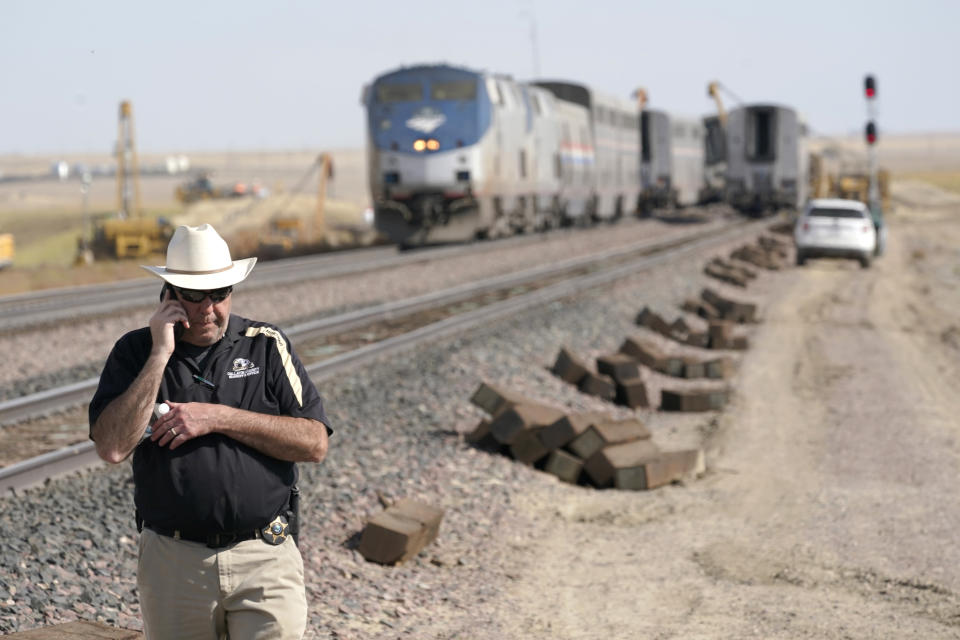 Jason Jarrett, of the Gallatin County (Mont.) Sheriff's Office, talks on a phone Sunday, Sept. 26, 2021, near an Amtrak train that derailed a day earlier just west of Joplin, Mont., killing three people and injuring others. The westbound Empire Builder was en route to Seattle from Chicago, with two locomotives and 10 cars. (AP Photo/Ted S. Warren)