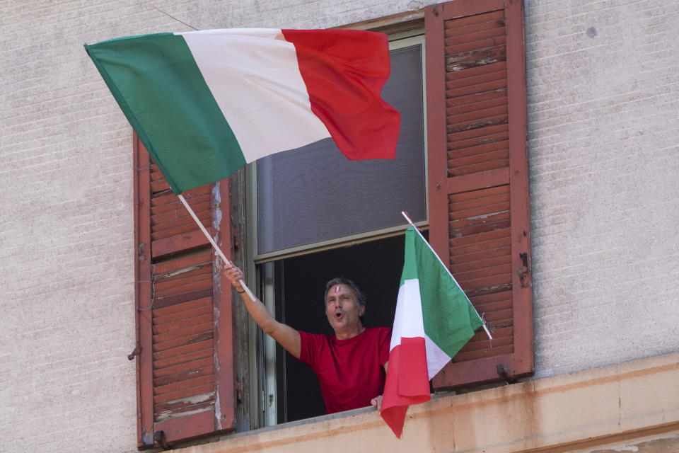 """A man waves the Italian flag as he chants from his window on the occasion of the 75th anniversary of Italy's Liberation Day, in Rome, Saturday, April 25, 2020. Italy's annual commemoration of its liberation from Nazi occupation is celebrated on April 25 but lockdown measures in the coronavirus-afflicted country mean no marches can be held this year and the National Association of Italian Partisans has invited all to sing """"Bella Ciao"""", the anthem of Italy's communist resistance, from their windows. (AP Photo/Andrew Medichini)"""