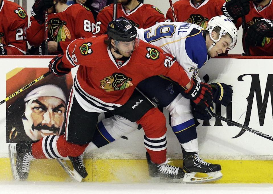 St. Louis Blues' Adam Cracknell, right, is checked by Chicago Blackhawks' Brandon Saad during the first period in Game 4 of a first-round NHL hockey playoff series in Chicago, Wednesday, April 23, 2014. (AP Photo/Nam Y. Huh)