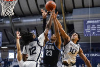 Villanova forward Jermaine Samuels (23) gos up for a rebound with Butler guard Myles Tate (12) and forward Bryce Nze (10) in the first half of an NCAA college basketball game in Indianapolis, Sunday, Feb. 28, 2021. (AP Photo/Michael Conroy)