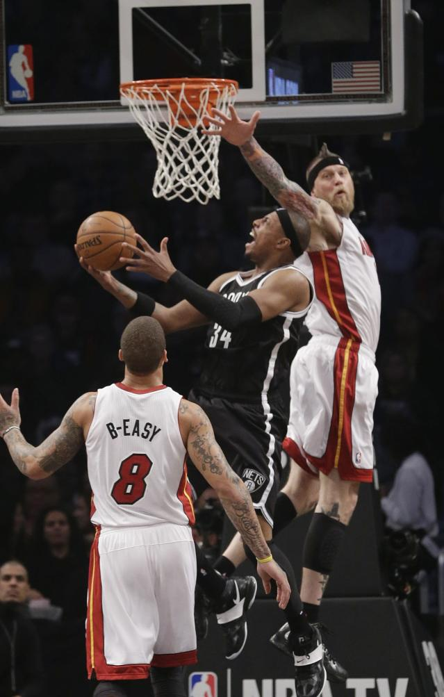 Brooklyn Nets' Paul Pierce (34) drives past Miami Heat's Chris Andersen (11) during the first half of an NBA basketball game on Friday, Jan. 10, 2014, in New York. (AP Photo/Frank Franklin II)