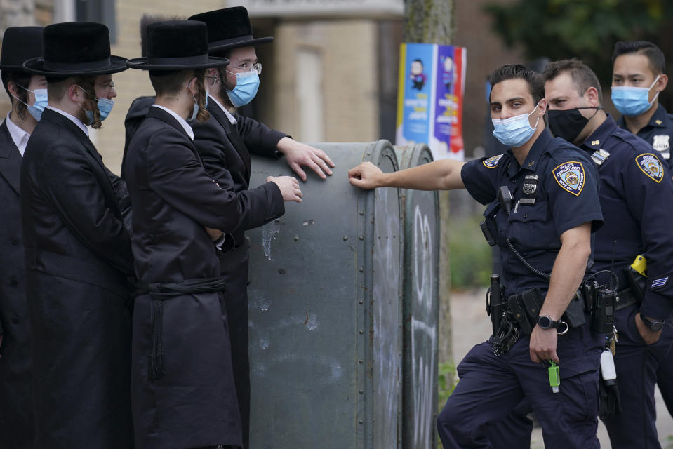 Members of the Orthodox Jewish community speak with NYPD officers, Wednesday, Oct. 7, 2020, in the Borough Park neighborhood of the Brooklyn borough of New York. Gov. Andrew Cuomo moved to reinstate restrictions on businesses, houses of worship and schools in and near areas where coronavirus cases are spiking. Many neighborhoods that stand to be affected are home to large enclaves of Orthodox Jews. (AP Photo/John Minchillo)