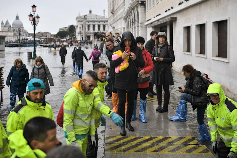 "Volunteers set up a footbridge for pedestrians across the flooded Riva degli Schiavoni embankment after an exceptional overnight ""Alta Acqua"" high tide water level, on November 13, 2019 in Venice. - Venice was hit by the highest tide in more than 50 years late November 12, with tourists wading through flooded streets to seek shelter as a fierce wind whipped up waves in St. Mark's Square. (Photo by Marco Bertorello / AFP) (Photo by MARCO BERTORELLO/AFP via Getty Images)"