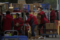 FILE - In this April 27, 2020, file photo, employees of a private delivery company sort out parcels at a distribution center in Beijing. Shortages of power, computer chips and other parts, soaring shipping costs and shutdowns of factories to battle the pandemic are taking a toll on Asian economies. (AP Photo/Andy Wong, File)