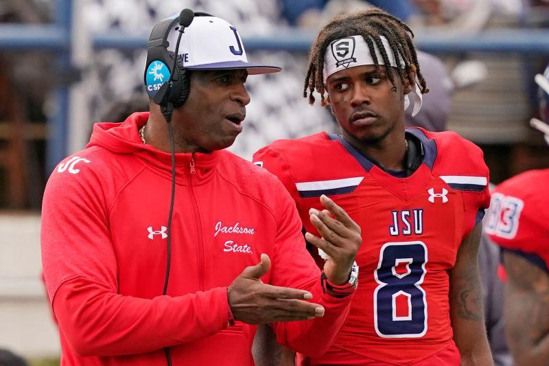 Jackson State football coach Deion Sanders, left, confers with quarterback Quincy Casey (8) during the second half of an NCAA college football game against Edward Waters in Jackson, Miss., Sunday, Feb. 21, 2021.