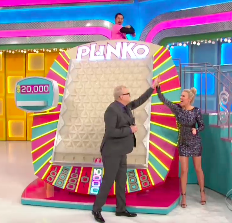 """Drew Carey and Rachel Reynolds celebrate a contestant landing on $10,000 playing Plinko on """"The Price Is Right."""""""