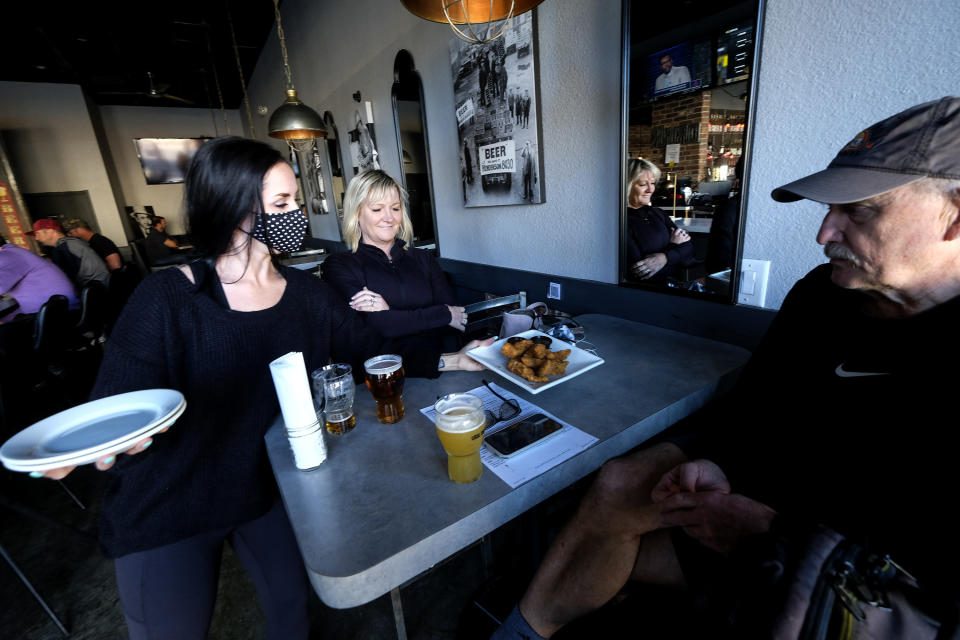 Waitress Penny Thompson, left, wearing a face mask serves Steve Zell, right, and his wife Julie at Notorious Burgers restaurant in Carlsbad, Calif., on Friday, Dec. 18, 2020. (AP Photo/Ringo H.W. Chiu)