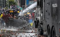 Police fire a water cannon at demonstrators in Bogota