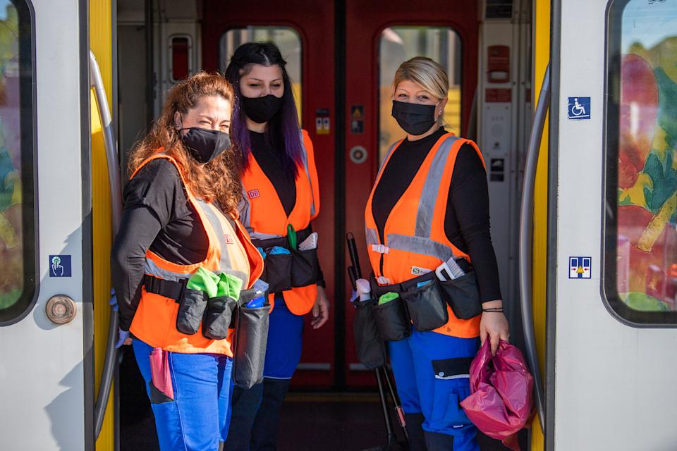 18 May 2020, Bavaria, Munich: Three cleaning staff of the mobile cleaning service of the Munich S-Bahn are standing in the door of a standing S-Bahn. As a team, the cleaning staff ensure that contact surfaces are properly disinfected during the corona period. Photo: Lino Mirgeler/dpa (Photo by Lino Mirgeler/picture alliance via Getty Images)