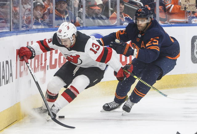New Jersey Devils' Nico Hischier (13) and Edmonton Oilers' Darnell Nurse (25) race to the puck during the first period of an NHL hockey game Friday, Nov. 8, 2019, in Edmonton, Alberta. (Jason Franson/The Canadian Press via AP)