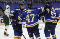 St. Louis Blues' Torey Krug (47) celebrates a goal with teammates Ivan Barbashev (49) and David Perron (57), as Minnesota Wild's Jordan Greenway (18) skates by, in the second period of an NHL hockey game, Wednesday, May 12, 2021 in St. Louis. (AP Photo/Tom Gannam)