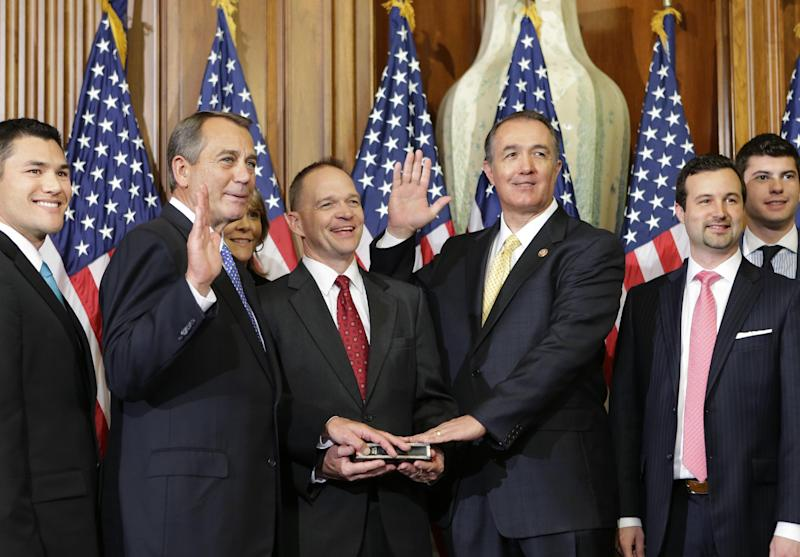 FILE - In this Jan. 3, 2013, file photo, Rep. Trent Franks, R-Ariz., center right, stands with his family for a ceremonial photo with Speaker of the House John Boehner, R-Ohio, center left, in the Rayburn Room of the Capitol after the new 113th Congress convened in Washington. A staffer for Rep. Franks, who is identified as Hispanic on the White House Press gallery list, told The Associated Press Franks doesn't consider himself Hispanic. But the conflicting numbers of hispanic members of congress illustrate just how elastic Hispanic identity can be, and how it might be pulled for political purposes as parties seek to appeal to the growing Hispanic electorate. (AP Photo/J. Scott Applewhite, File)