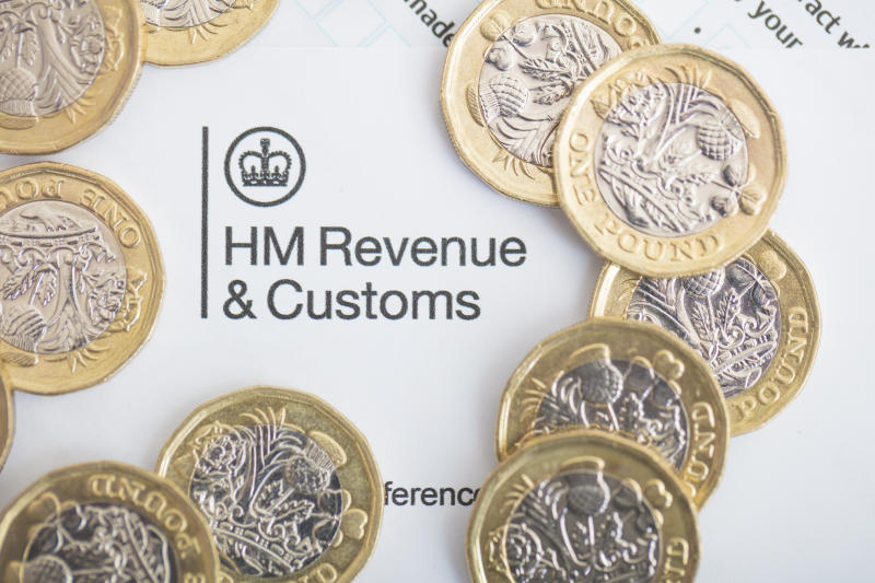 An editorial stock photo of the UK Inland Revenue Tax forms with the new 2017 One Pound Coins.