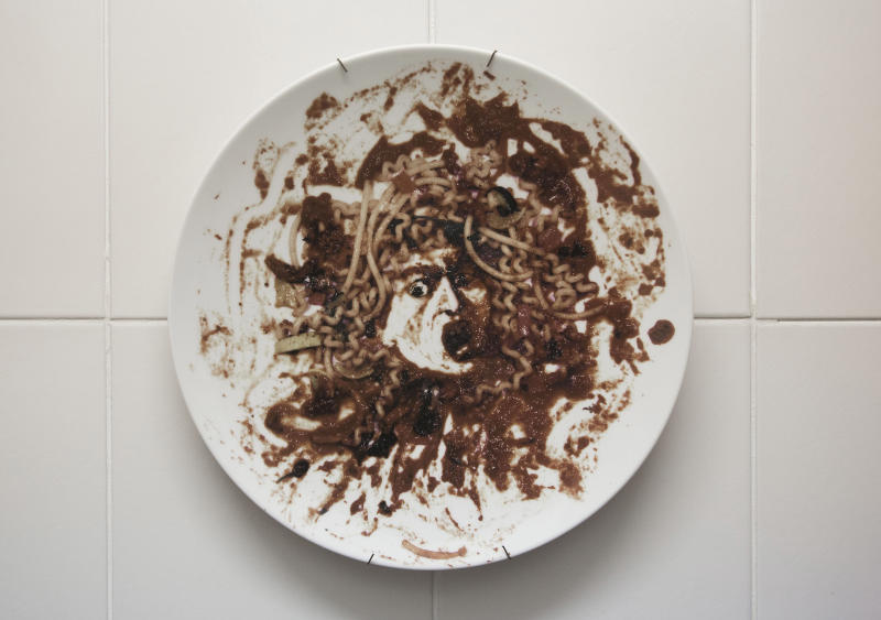 In this Aug. 21, 2012 photo, a plate by Brazilian artist Vik Muniz that features his recreation of Caravaggio's Medusa hangs on the kitchen wall at the home of Beto Silva, a luxury clothing store salesman, in Rio de Janeiro, Brazil. Like other thriving middle-class Brazilians, Silva has bought his way into the growing ranks of collectors who are helping to put Rio de Janeiro on the international art map. (AP Photo/Felipe Dana)
