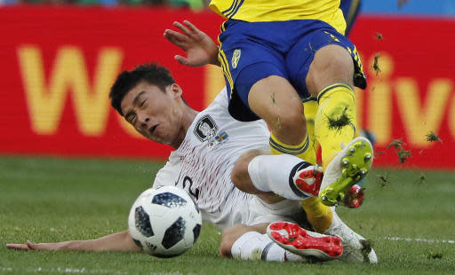 Sweden's Viktor Claesson is challenged by South Korea's Lee Yong during the group F match between Sweden and South Korea at the 2018 soccer World Cup in the Nizhny Novgorod stadium in Nizhny Novgorod, Russia, Monday, June 18, 2018. (AP Photo/Pavel Golovkin)