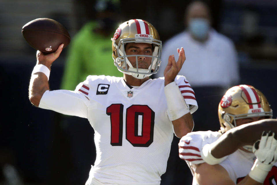 FILE - In this Sunday, Nov. 1, 2020, file photo, San Francisco 49ers quarterback Jimmy Garoppolo passes against the Seattle Seahawks during the first half of an NFL football game in Seattle. The San Francisco 49ers have made a big move to grab their quarterback of the future by trading up with Miami for the No. 3 pick in next month's draft. Drafting a quarterback would likely lead to the end of Jimmy Garoppolo's tenure in San Francisco either in a trade this season or after a year if the Niners opt to keep a veteran to help ease the transition for a rookie QB. (AP Photo/Scott Eklund, File)
