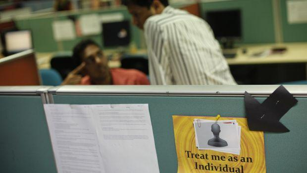 Employees work behind sign on floor of outsourcing company WNS in Mumbai