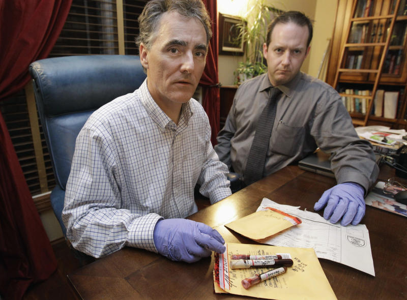 FILE - In this Nov. 30, 2012 file photo, Cook County Sheriff Tom Dart, left, and sheriff's detective Jason Moran are seen in Chicago with three recently discovered vials of mass murderer John Wayne Gacy's blood. Dart says his officers and the FBI using high tech equipment and two dogs trained to sniff out human remains, went to the apartment complex of Gacy's late mother in March 2013 and found nothing to indicate the serial killer stashed any bodies there. Dart has been investigating the serial killer who was convicted in 1980 of murdering 33 young men in the 1970s on a number of fronts the last couple years. (AP Photo/M. Spencer Green, File)
