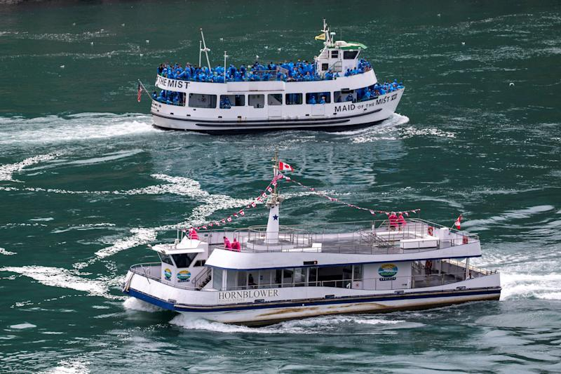 American tourist boat Maid Of The Mist, limited to 50 per cent occupancy under New York state's rules amid the spread of the coronavirus disease (COVID-19), glides past a Canadian vessel limited under Ontario's rules to just six passengers, in Niagara Falls, Ont. on July 21, 2020. (Photo: Carlos Osorio / Reuters)