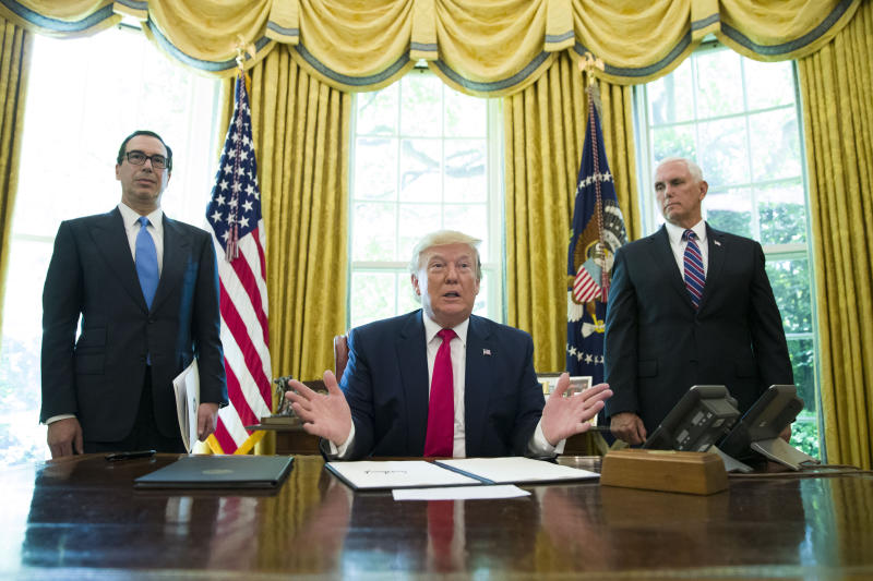 President Donald Trump listens to a reporter's question after signing an executive order to increase sanctions on Iran, in the Oval Office of the White House, Monday, June 24, 2019, in Washington. Trump is accompanied by Treasury Secretary Steve Mnuchin, left, and Vice President Mike Pence. (AP Photo/Alex Brandon)