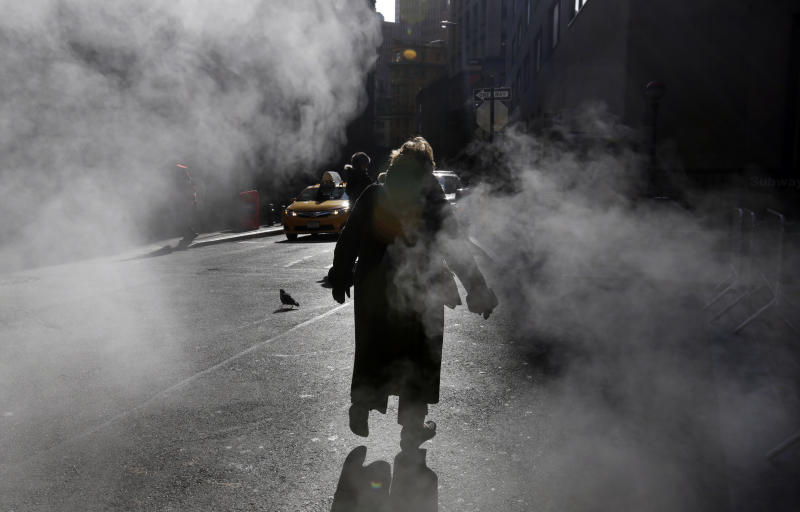 A woman crosses Wall Street between amid the steam, in New York's Financial District, Wednesday, Jan. 23, 2013. A cold wave with sub-zero temperatures was expected to keep its icy grip on much of the eastern U.S. into the weekend before seasonable temperatures bring relief. (AP Photo/Richard Drew)