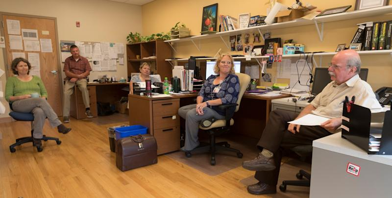 After a morning of driving around visiting patients, physician James DeLine, right, updates the staff at his clinic.
