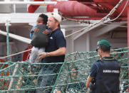 A migrant child is carried as he disembarks the Ocean Viking, docked at the Sicilian port of Messina, southern Italy, Tuesday, Sept. 24, 2019. The humanitarian ship has docked in Sicily, Italy, to disembark 182 men, women and children rescued in the Mediterranean Sea after fleeing Libya. (Carmelo Imbesi/ANSA via AP)