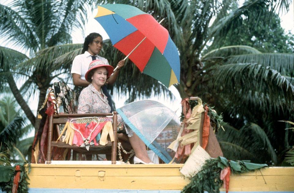 <p>The Queen is carried in a Canoe to the shore of Tuvalu at the end of her visit to the South Sea Islands in 1982. (PA Archive) </p>