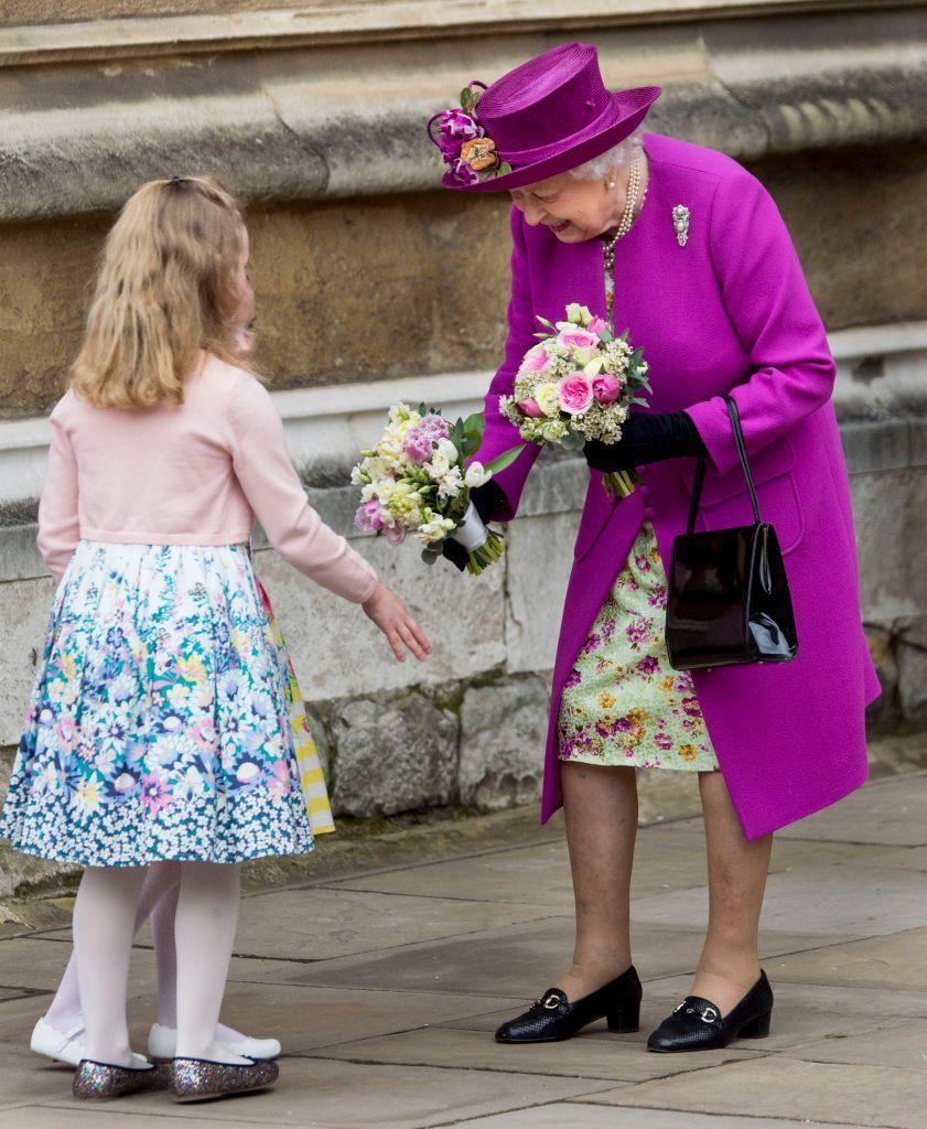<p>The Queen receives flowers from children outside of St. George's Chapel.</p>
