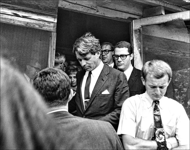 <p>Kennedy and his aide, Peter Edelman (in glasses behind Kennedy), visit several homes in Cleveland, Miss., on April 11, 1967. (Photo: Dan Guravich) </p>