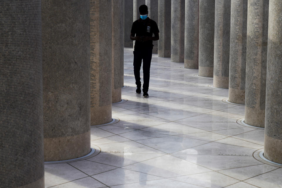 """A worker walks through an installation honoring the foreign laborers who built Expo 2020 in Dubai, United Arab Emirates, Sunday, Oct. 3, 2021. Dubai's Expo 2020 on Saturday, Oct. 2, 2021, offered conflicting figures for how many workers had been killed on site during construction of the massive world's fair, first saying five and then later three. In a later statement, Expo apologized and described the initial figure as a """"mistake."""" (AP Photo/Jon Gambrell)"""