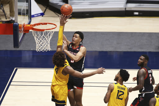 Red Raiders guard Micah Peavy (5) shoots while defended by West Virginia guard Miles McBride (4) during the second half of an NCAA college basketball game Monday, Jan. 25, 2021, in Morgantown, W.Va. (AP Photo/Kathleen Batten)