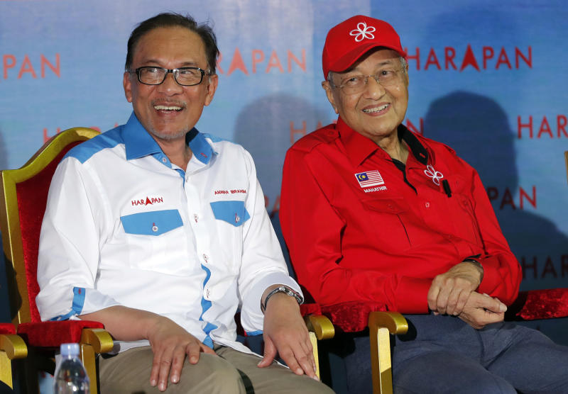 FILE - In this Oct. 8, 2018, file photo, Malaysia's Prime Minister Mahathir Mohamad, right, sits next to Malaysia's reform icon Anwar Ibrahim during a rally in Port Dickson. Political tension is building in Malaysia amid talks that Mahathir will pull his party out of the ruling alliance and team up with opposition parties to form a new government in a major political upheaval. It will thwart his named successor Anwar Ibrahim from taking over. (AP Photo/Vincent Thian)