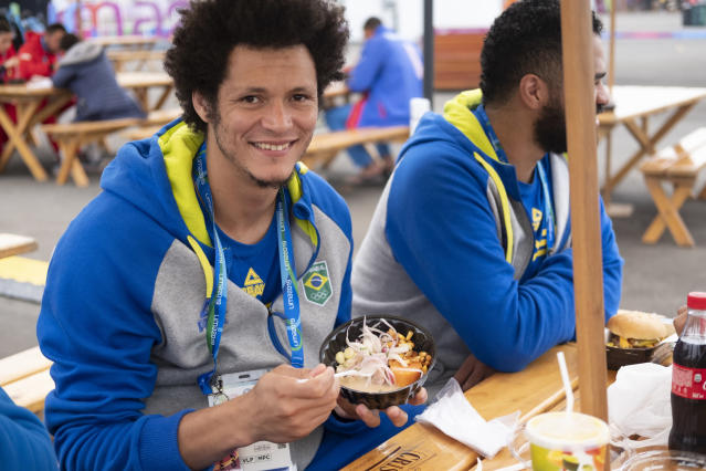In this Aug. 3, 2019 photo, Thiagus Petrus, a member of the Brazilian handball team poses for photos while he takes a break from eating ceviche at the international center outside the Pan American athletes' village in Lima, Peru. Peruvian food was the star at the recent Pan Am Games. Athletes from 41 countries across the Americas tasted the highly-regarded cuisine that blends indigenous traditions with European, African and Asian influences with an abundance of seafood from the Pacific Ocean's cold Humboldt current. (AP Photo/Luis Andres Henao)