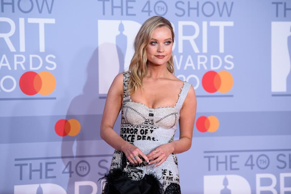 Laura Whitmore back from South Africa, where she's filming <em>Love Island</em>, for a short time only. She opted for a £1,850 Clio Peppiat newspaper print mini dress and, as is proving quite popular at the Brits, a feathered bag. (Getty Images)