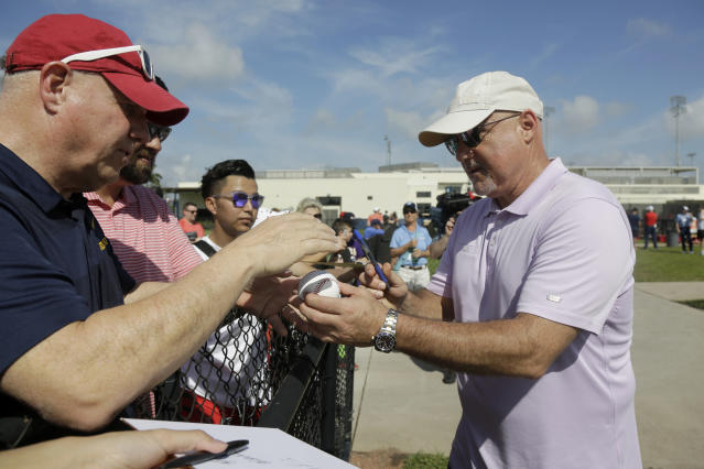 Washington Nationals general manager Mike Rizzo, right, signs autographs for fans during spring training baseball practice Friday, Feb. 14, 2020, in West Palm Beach, Fla. (AP Photo/Jeff Roberson)