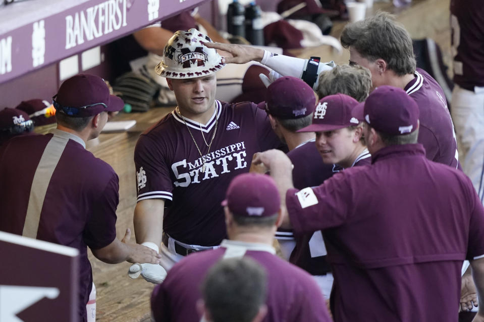 Mississippi State's Logan Tanner, center left, celebrates with teammates after hitting a second-inning three-run home run against Notre Dame during an NCAA college baseball super regional game, Monday, June 14, 2021, in Starkville, Miss. (AP Photo/Rogelio V. Solis)