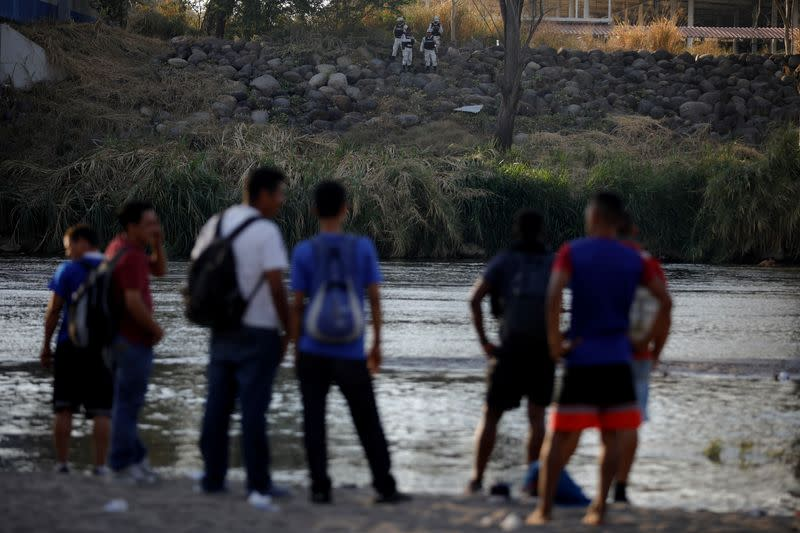 Migrants travelling to the U.S. gather by the Suchiate river as they are watched by members of the mexican National guard, at the border between Guatemala and Mexico, in Tecun Uman