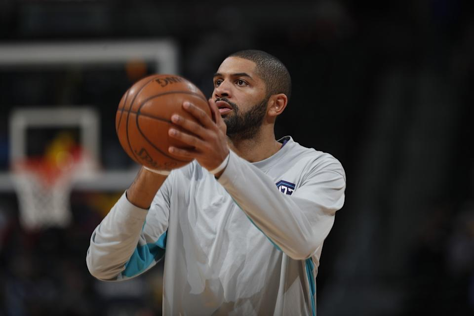Nicolas Batum holds the basketball as he warms up before a game.