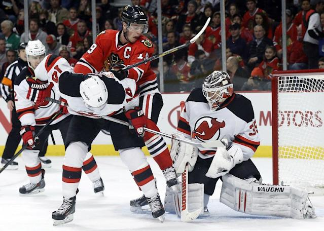 Chicago Blackhawks center Jonathan Toews (19) pushes New Jersey Devils center Adam Henrique (14) while goalie Cory Schneider makes a save during the second period of an NHL hockey game Monday, Dec. 23, 2013, in Chicago. (AP Photo/Charles Rex Arbogast)