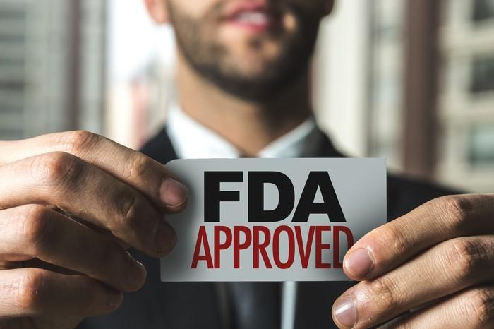 """Businessman holding """"FDA approved"""" card"""