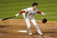 Los Angeles Angels' Shohei Ohtani, right, loses his helmet as swings on a dropped strike three during the sixth inning of a baseball game against the Texas Rangers Monday, April 19, 2021, in Anaheim, Calif. (AP Photo/Mark J. Terrill)