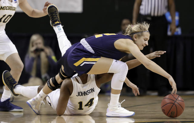 Northern Colorado guard Savannah Scott (2) steps over Michigan guard Akienreh Johnson (14) to reach a loose ball during the first half of a first-round game at the NCAA women's college basketball tournament in Waco, Texas, Friday, March 16, 2018. (AP Photo/Tony Gutierrez)
