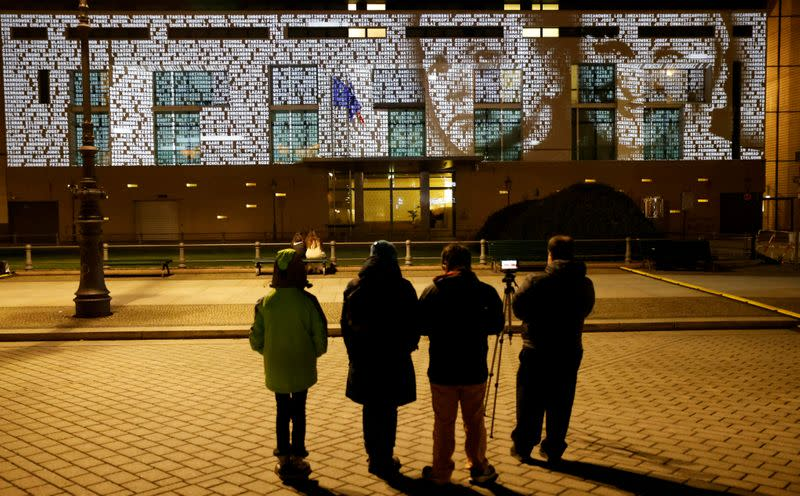 FILE PHOTO: People watch at a light installation called #everynamecounts projecting names of victims of the Nazi regime in Berlin