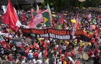 """Demonstrators rally alongside a banner with a message that reads in Portuguese: """"vaccine and jobs, democracy and impeachment, Bolsonaro get out"""", during a protest against Brazilian President Jair Bolsonaro, calling for his impeachment over his government handling of the pandemic and accusations of corruption in the purchases of COVID-19 vaccines in Sao Paulo, Brazil, Saturday, Oct. 2, 2021. (AP Photo/Andre Penner)"""
