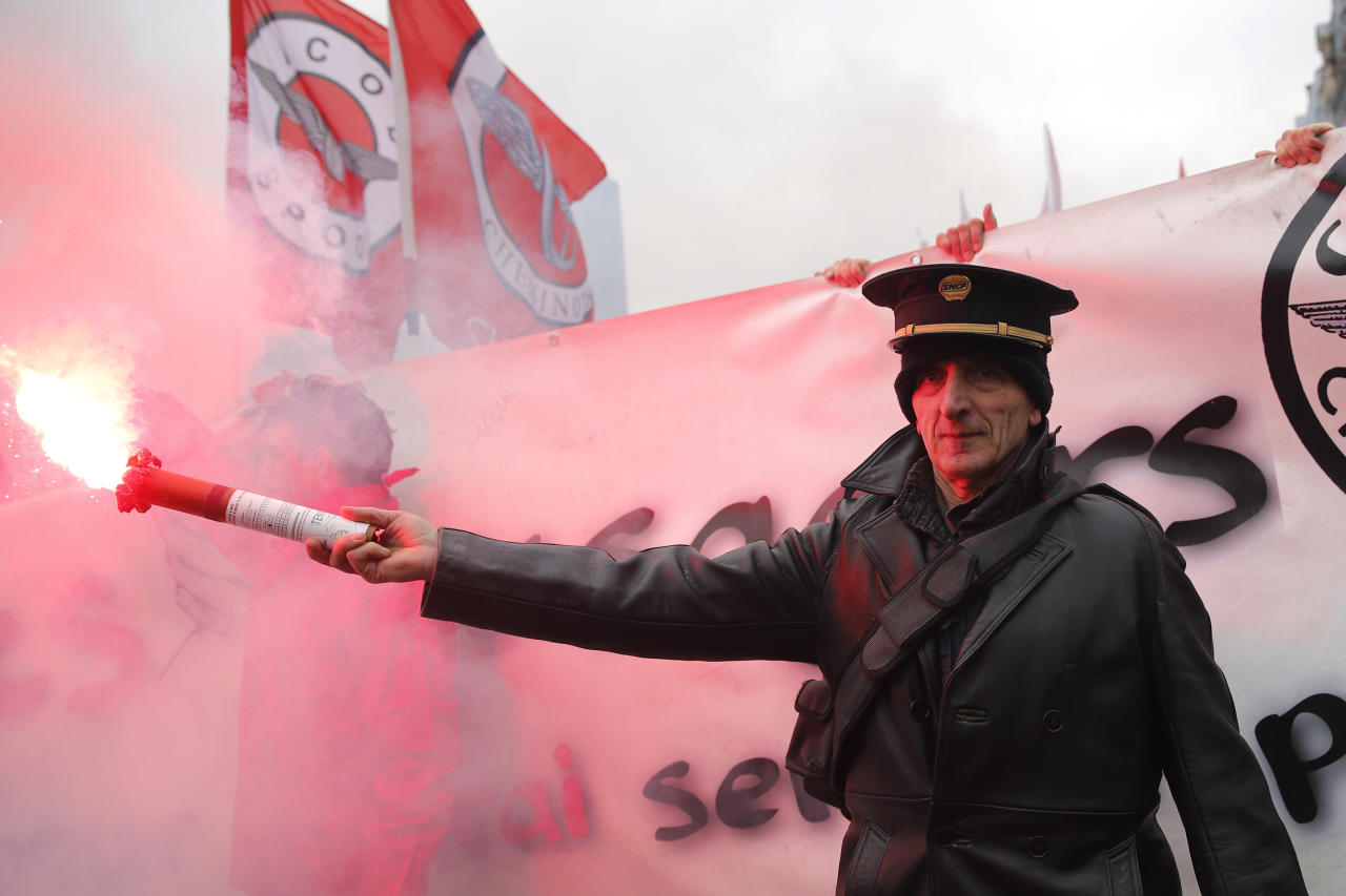 <p> A demonstrator holds a flare as French railway workers gather at the Gare de l'Est train station before marching in the streets of Paris, France, Thursday, March 22, 2018. Employees of the national railway company SNCF reject a government plan aimed at adapting the company ahead of opening the service to competition. (AP Photo/Christophe Ena) </p>