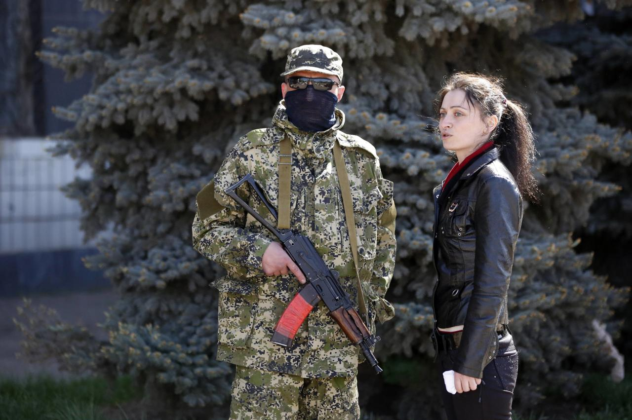 A pro-Russian armed man talks with a woman in front of seized town administration building in Kostyantynivka April 28, 2014. Armed pro-Russian separatists who took control of the police headquarters in the east Ukrainian town of Kostyantynivka have also seized the town administration building, a spokesman for the regional government said. REUTERS/Marko Djurica (UKRAINE - Tags: POLITICS CIVIL UNREST)